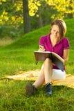Schöne Frau, die in ihr Tagebuch lacht und schreibt Stockfotos