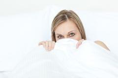 Schöne Frau, die in ihrem Bett versteckt Lizenzfreie Stockfotos