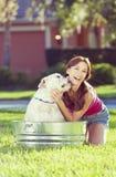 Schöne Frau, die ihren Haustier Hund in einer Wanne wäscht stockfotografie