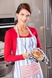 Schöne Frau, die ihren Kuchen zeigt Stockfoto