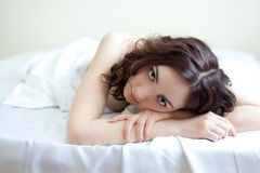Schöne Frau, die im Bett liegt Stockbild