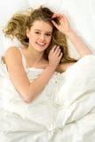 Schöne Frau, die im Bett liegt Lizenzfreies Stockbild