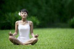 Schöne Frau, die im Garten meditiert Stockfotos
