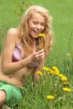 Schöne Frau, die im Gras und in den Blumen sich entspannt Lizenzfreies Stockfoto