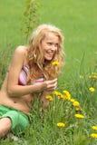 Schöne Frau, die im Gras und in den Blumen sich entspannt Stockfotos