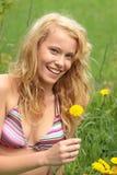 Schöne Frau, die im Gras und in den Blumen sich entspannt Lizenzfreies Stockbild