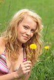 Schöne Frau, die im Gras und in den Blumen sich entspannt Lizenzfreie Stockfotografie