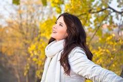 Schöne Frau, die im Herbstpark genießt stockfoto