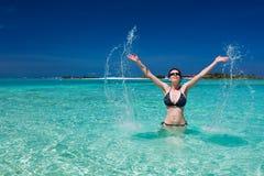 Schöne Frau, die im Meer spritzt lizenzfreie stockfotografie