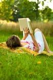Schöne Frau, die im Park sich entspannt Lizenzfreies Stockbild
