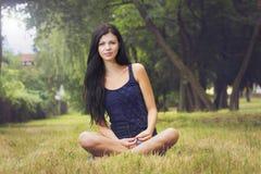 Schöne Frau, die im Park sitzt Stockfotos