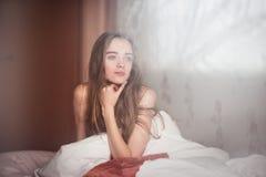 Schöne Frau, die im Schlafzimmer nach gutem Nachtschlaf aufwacht Stockfotografie