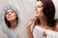 Schöne Frau, die im Spiegel schaut Lizenzfreie Stockfotos