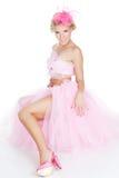 Schöne Frau, die im Studio in einem rosafarbenen Kleid aufwirft Stockfotos