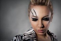 Schöne Frau, die im Studio im Zebramantel aufwirft stockbild
