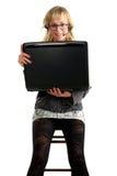 Schöne Frau, die im Stuhl mit Laptop sitzt Lizenzfreie Stockfotos