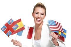 Schöne Frau, die internationale Flaggen zeigt Lizenzfreies Stockfoto