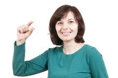 Schöne Frau, die kleine Sachegeste zeigt Lizenzfreie Stockfotos