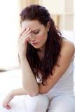 Schöne Frau, die Kopfschmerzen im Bett hat Stockbilder
