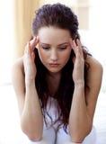 Schöne Frau, die Kopfschmerzen im Bett hat Lizenzfreie Stockfotos