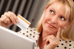 Schöne Frau, die Laptop-Holding-Kreditkarte verwendet Stockfoto