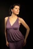 Schöne Frau, die lila Kleid und das Tanzen trägt Stockfotografie