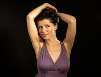 Schöne Frau, die lila Kleid und das Tanzen trägt Lizenzfreie Stockfotos