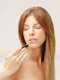 Schöne Frau, die Lippenstift mit Pinsel anwendet Lizenzfreies Stockfoto