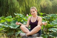 Schöne Frau, die in Lotosstellung im Garten sitzt lizenzfreie stockfotos