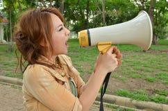 Schöne Frau, die in Megaphon im Park kreischt Lizenzfreie Stockfotos