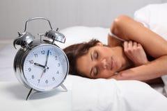 Schöne Frau, die mit der Alarmuhr nahe gelegen schläft Stockbild