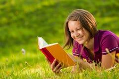 Schöne Frau, die mit einem Buch im Park lacht Stockbild