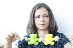 Schöne Frau, die mit Spielwaren in ihren Händen lächelt Lizenzfreie Stockfotografie