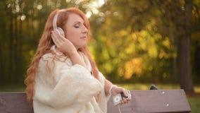 Schöne Frau, die Musik auf Kopfhörern hört stock video footage