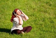 Schöne Frau, die Musik mit Kopfhörern hört Stockbild