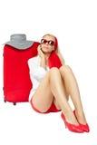 Schöne Frau, die nahe bei rotem Koffer sitzt Lizenzfreie Stockfotografie