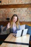 Schöne Frau, die nahe Holztisch mit weißem Laptop und Tasse Kaffee im gemütlichen Café sitzt Lizenzfreie Stockfotografie