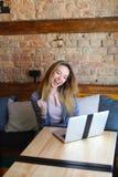 Schöne Frau, die nahe Holztisch mit weißem Laptop und Tasse Kaffee im gemütlichen Café sitzt Stockfoto