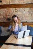 Schöne Frau, die nahe Holztisch mit weißem Laptop und Tasse Kaffee im gemütlichen Café sitzt Lizenzfreies Stockfoto