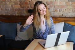 Schöne Frau, die nahe Holztisch mit weißem Laptop und Tasse Kaffee im gemütlichen Café sitzt Stockfotos