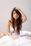 Schöne Frau, die oben im Bettschlechthaar sitzt stockfoto