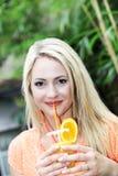 Schöne Frau, die orange Cocktail trinkt Lizenzfreie Stockfotos