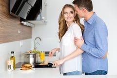 Schöne Frau, die Pfannkuchen macht und mit Ehemann flirtet Lizenzfreie Stockbilder