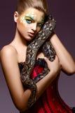 Schöne Frau, die Pythonschlange-Schlange in den Händen - Leistung anhält lizenzfreie stockfotografie
