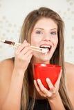 Schöne Frau, die Reis mit Steuerknüppeln isst Stockfotos