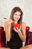 Schöne Frau, die Reis mit Steuerknüppeln isst Stockbild