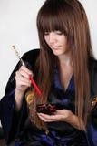Schöne Frau, die rote Ess-Stäbchen anhält Lizenzfreies Stockbild