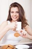 Schöne Frau, die Tee und Plätzchen genießt Lizenzfreies Stockbild