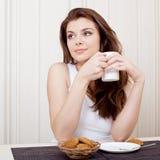 Schöne Frau, die Tee und Plätzchen genießt Stockbild