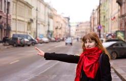 Schöne Frau, die versucht, ein Fahrerhaus in der Stadt zu hageln Lizenzfreies Stockbild